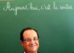 French President Francois Hollande smiles as he sits to chair a round table discussion on the changes in the school timetable set out by the government during a visit to Michelet school in Denain on September 3, 2013. 'Today, it's back to school' is written on the board.  AFP PHOTO / POOL / DENIS CHARLET        (Photo credit should read DENIS CHARLET/AFP/Getty Images)